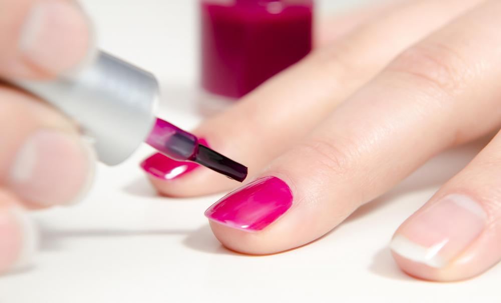 Pink nail polish being applied.